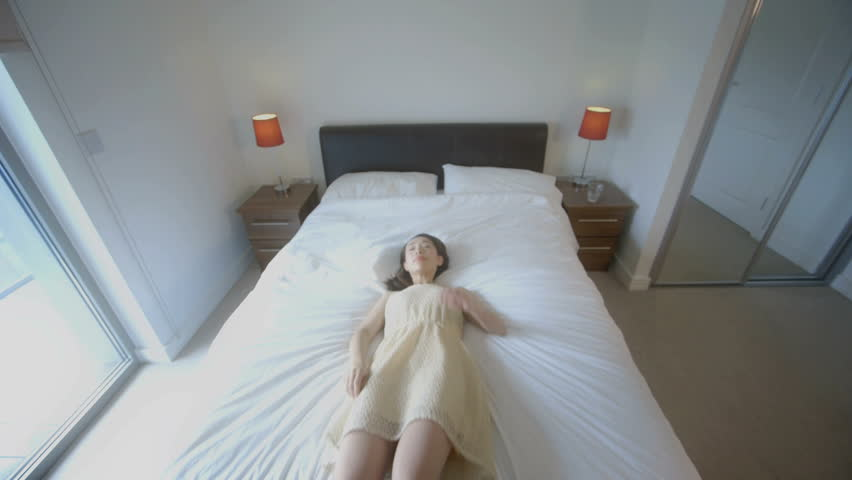 MS Young woman jumps backwards onto bed