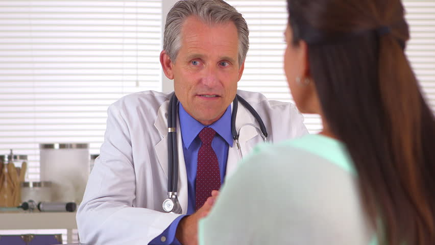 Doctor asking patient questions in his office