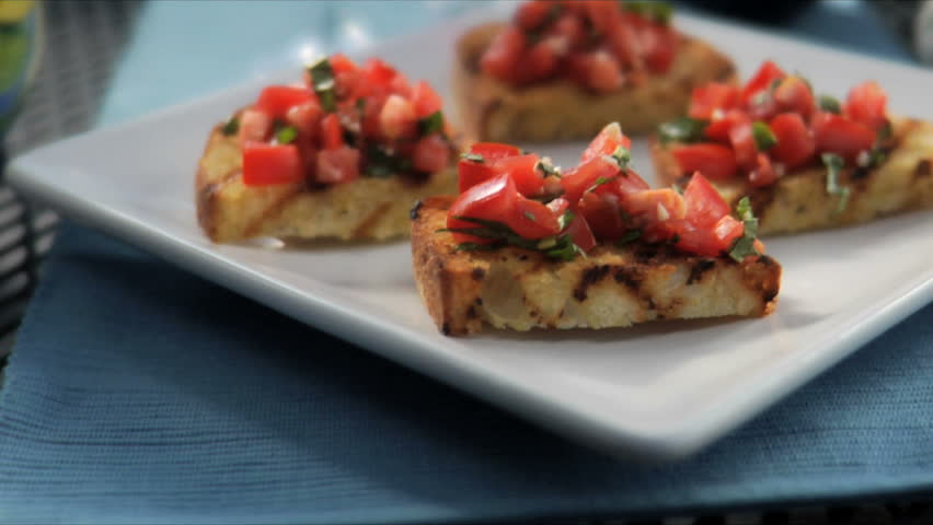 Close up of a classic Italian bruschetta, tomato and onion on toasted bread, sitting on a table with wine behind it