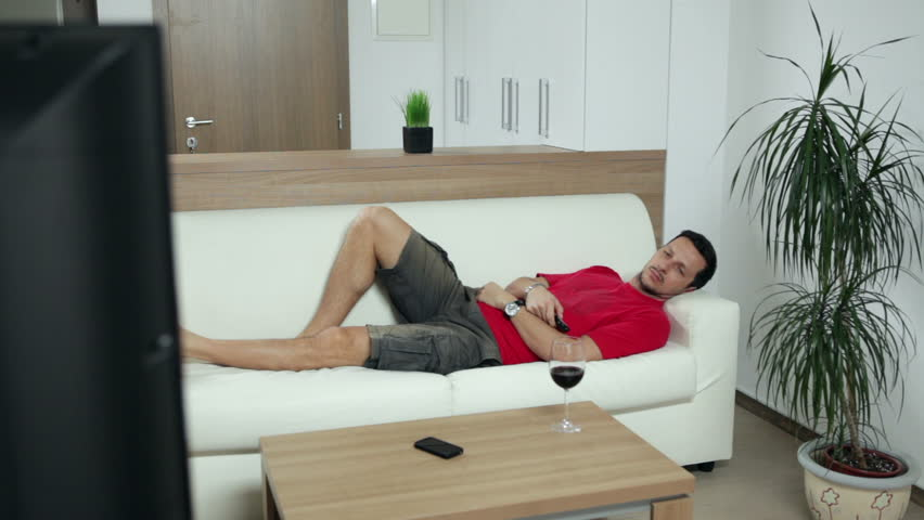 Man lying on couch at home and watching an entertaining program on TV. High definition video. | Shutterstock HD Video #4799000