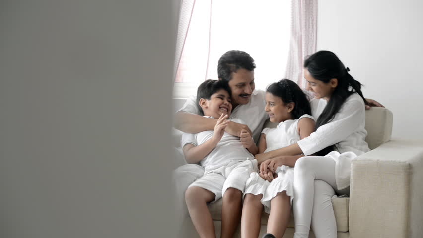 Pan shot of an Indian family spending time together on a couch