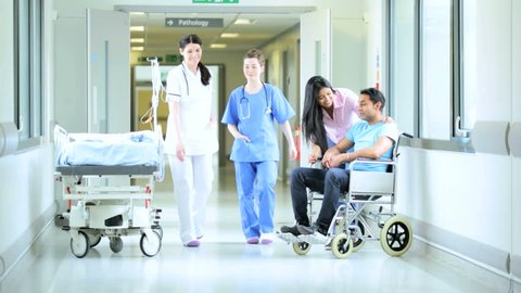 Female nursing staff walking through hospital corridor passing young South Asian family spending quality time together