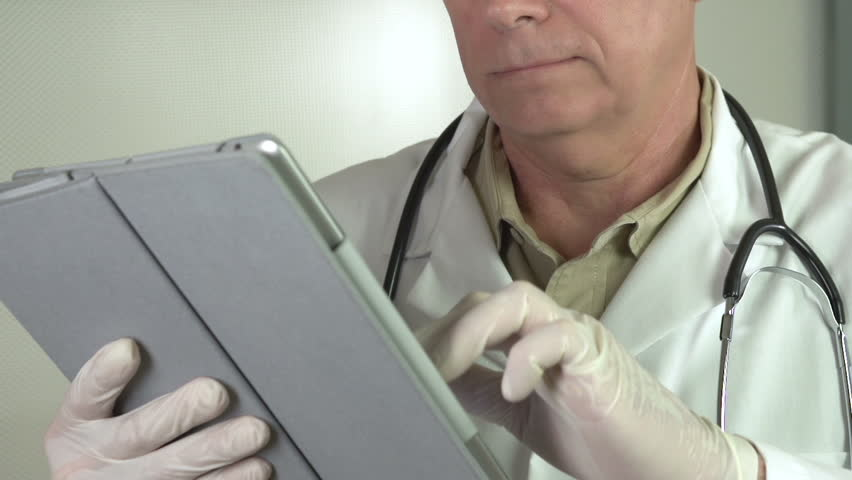 Mature doctor using tablet smiles at camera | Shutterstock HD Video #4810400