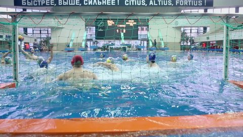 MOSCOW - APR 20: Man tries to score goal during match of teams Astana and Dynamo on water polo in basin of Olympic Sports complex on 20 April 2012 in Moscow, Russia. Water polo invented at UK in XIX