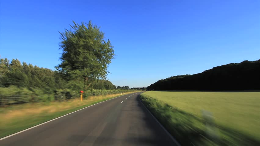 Driving a Car - Driving through a rural landscape in Germany. Shot with a roof-mounted camera, the car is driving with moderate speed.