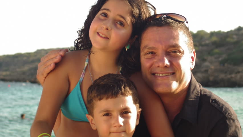 A father smiles at the camera with his daughter and son in front of the ocean | Shutterstock HD Video #4822220