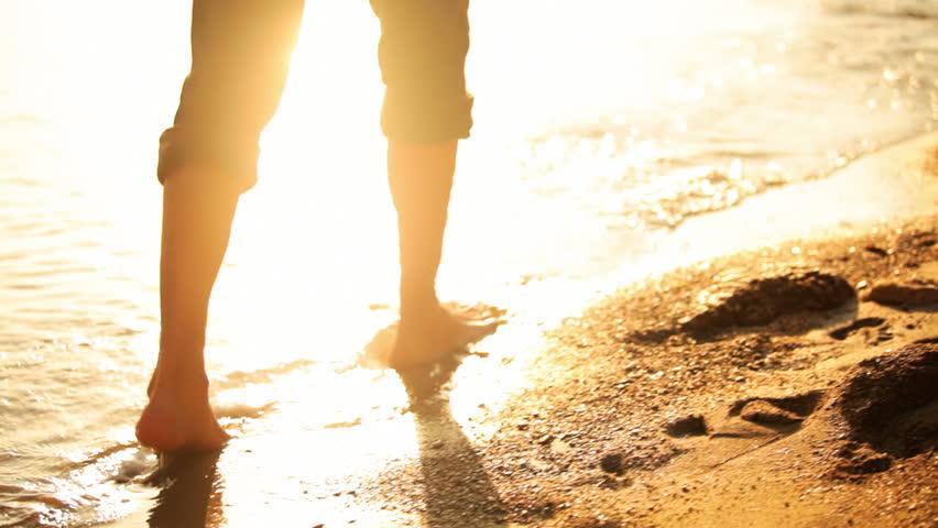 Shot of a man's legs walking down the beach through the water at dusk