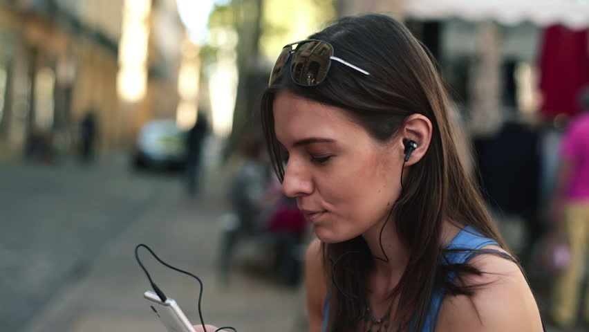 Woman listening to music on her smartphone in the city