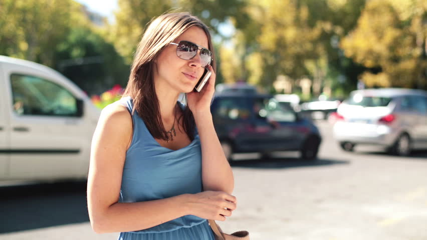Happy attractive woman talking on cellphone by city street