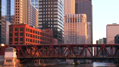 The El train travels over a bridge in front of the Chicago skyline.
