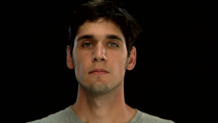A young man looks up with a blank stare on a black background