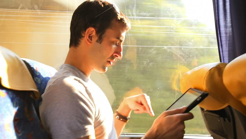 A young man looks through his tablet as he takes a bus ride