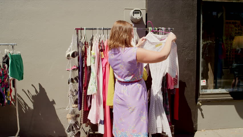 Woman shopping for clothes at an outdoor market | Shutterstock HD Video #4867094