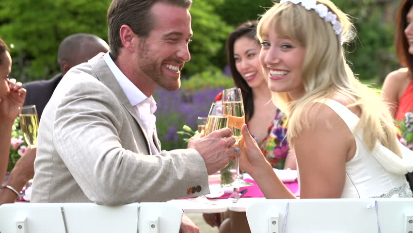 Slow motion tilt from Mr & Mrs signs to smiling bride and groom at outdoor wedding party reception