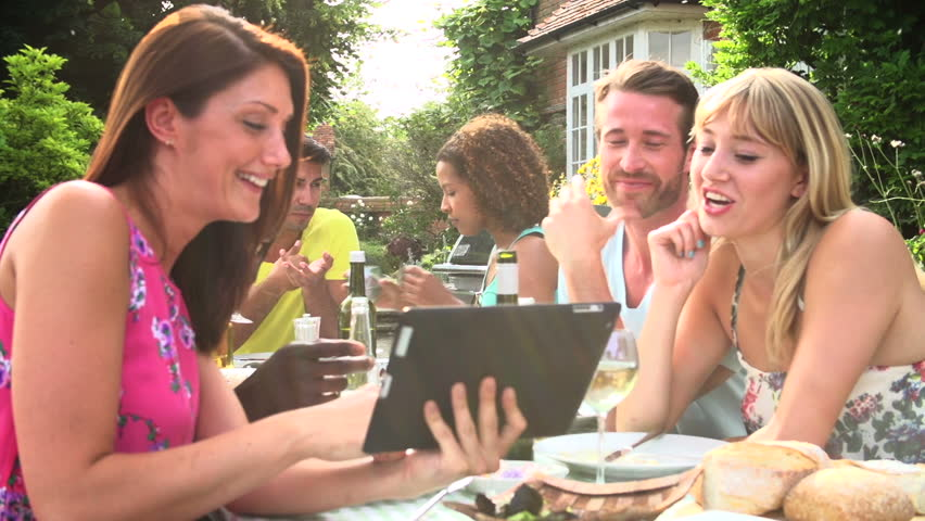 Adult friends around table enjoying summer barbecue and looking at digital tablet