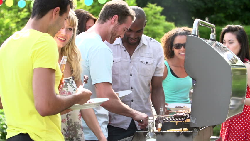 Men serving burgers, kabobs, and corn from backyard barbecue for summertime dinner party
