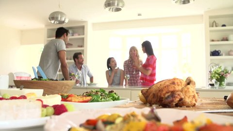 Group of friends at dinner party drinking wine in background behind delicious buffet