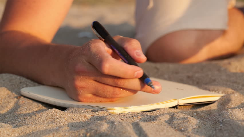 Man writing in his diary at the beach while lying on the golden sand, close up view of the book and his hand holding a pen
