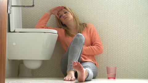 Hung over teenage girl sits on floor of bathroom feeling unwell before throwing up in the toilet
