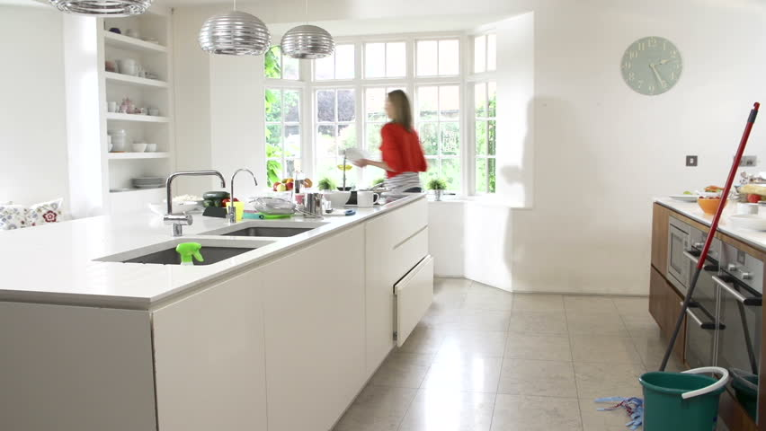 Time lapse sequence of woman performing a range of domestic chores in kitchen before sitting and relaxing with digital tablet and hot drink.