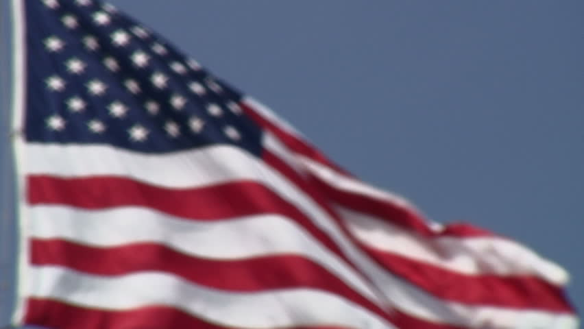 Rack focus from blurry to sharp American flag blowing in the wind