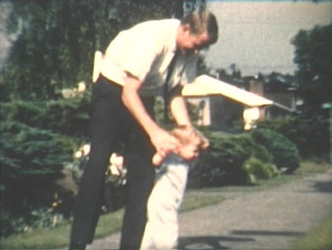 1960s home video of father helping toddler son learn to walk in Seattle, Washington neighborhood.
