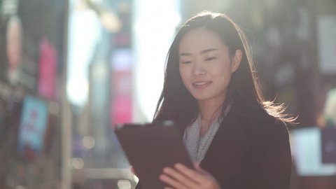 Asian woman in New York City Times Square street using ipad tablet pc