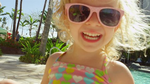 A young girl wearing sunglasses at the pool smiles and laughs at the camera