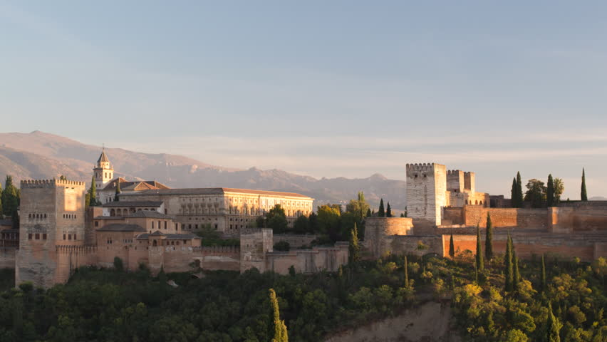 Day to night Time lapse of the beautiful alhambra palace in granada with the sierra nevada mountains in the distance