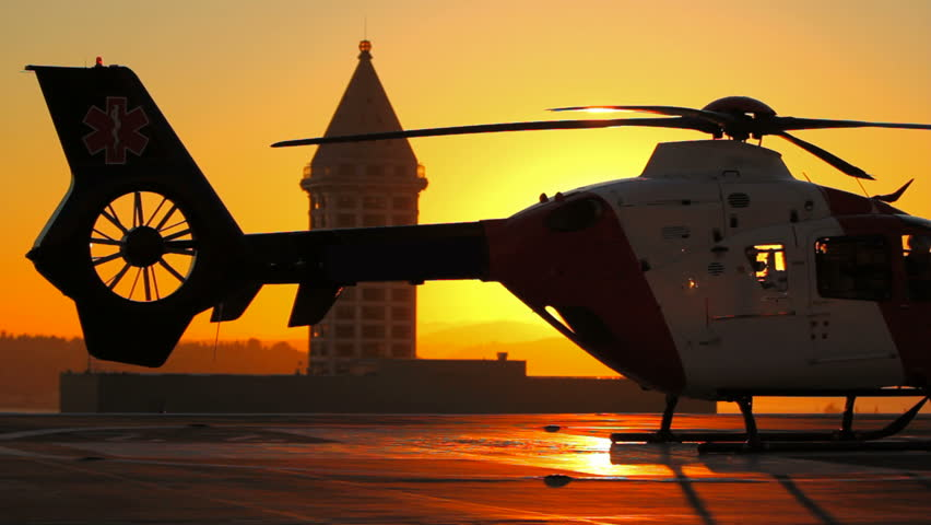 Medevac helicopter starting with beautiful backlit sunset.