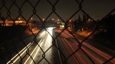 Time Lapse of Traffic through Chain Link Fence - 4K