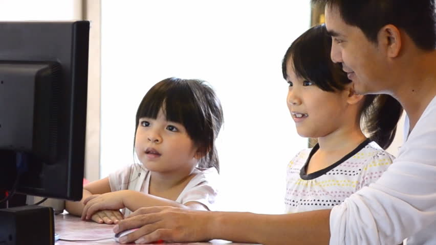 Asian Father And Cute Daughters Playing Computer