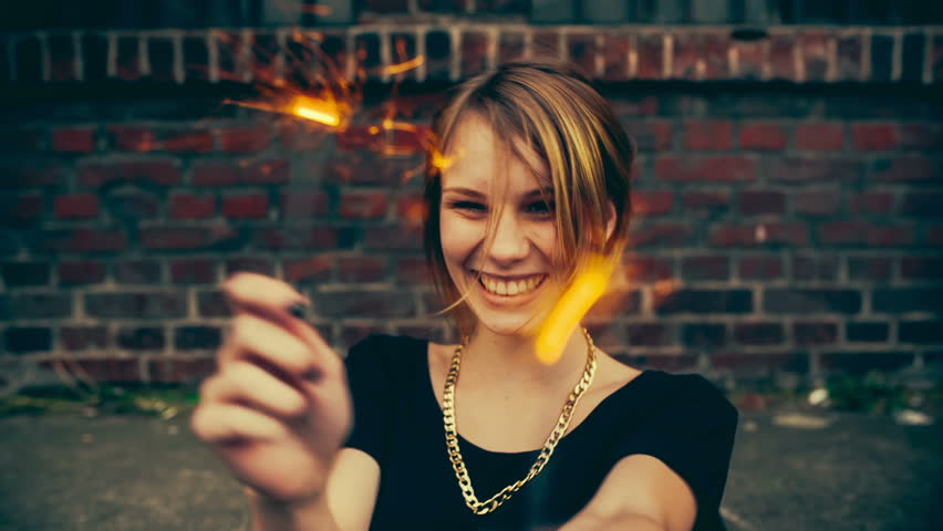 Teenage hipster girl having fun with sparkles with vintage color correction
