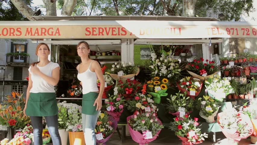 Two family sisters business owners opening the florist kiosk small business store and preparing and setting up the shop, working together outdoors during a sunny day, time lapse.