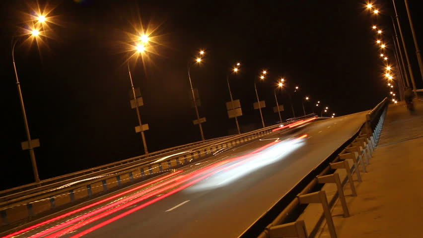 Tilted time-lapse driving cars, night city highway yellow lights