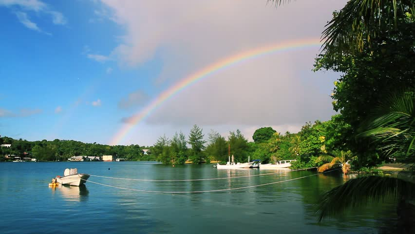 Small inlet with boat and Rainbow after a storm on Yap, Federated States of Micronesia