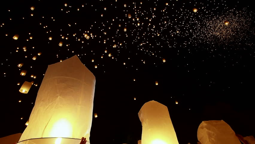 Loy Krathong festival in Chiang Mai, Thailand, hands releasing hot air balloon into the night sky.