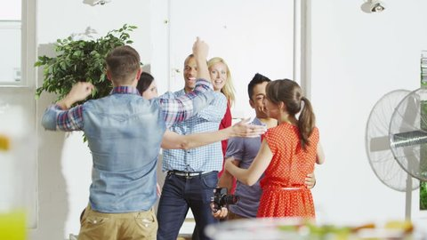 Friendly couple hosting a party at home greet their guests as they arrive. In slow motion.