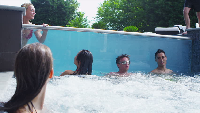 Excited group of young friends enjoying a pool party at swimming pool with clear glass panel and hot tub. In slow motion.