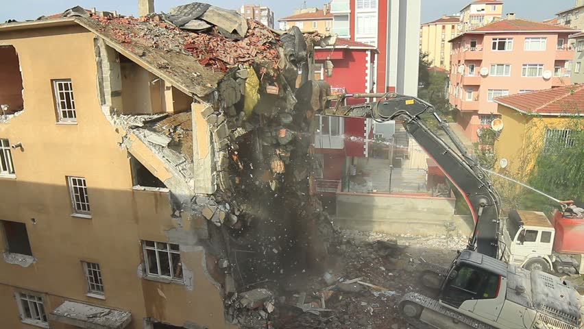Apartment building demolition using an excavator with telescopic arm attachment. Most buildings in the country still fail to meet basic safety standards against an earthquake.