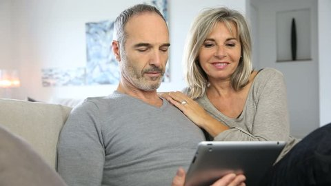 Mature couple at home websurfing with tablet