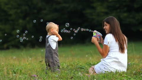 Lovely baby have fun, run to catch the soap bubbles, soap balloons