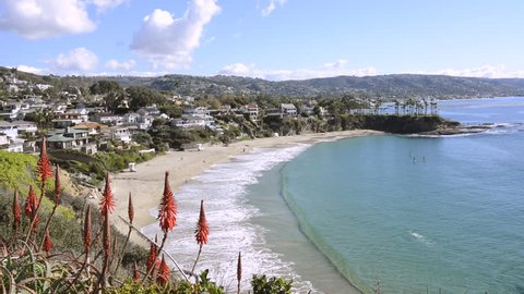 A beautiful cliff side view of Crescent Bay Beach in Laguna Beach, California shows the scenic, turquoise water and the white sand beach.