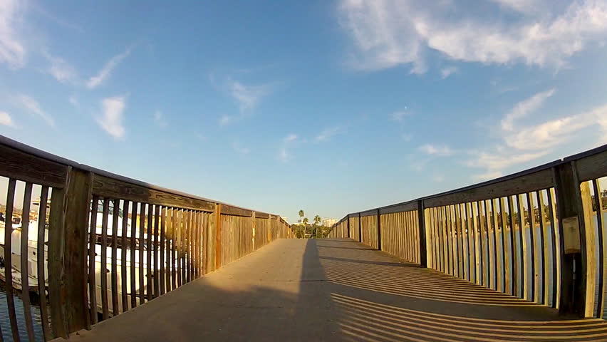 First person view of man riding a bicycle on a wooden bridge next to a marina in Newport Beach, California. This clip features a shadow of himself and his bike cast on the bridge railings next to him. | Shutterstock HD Video #5188679