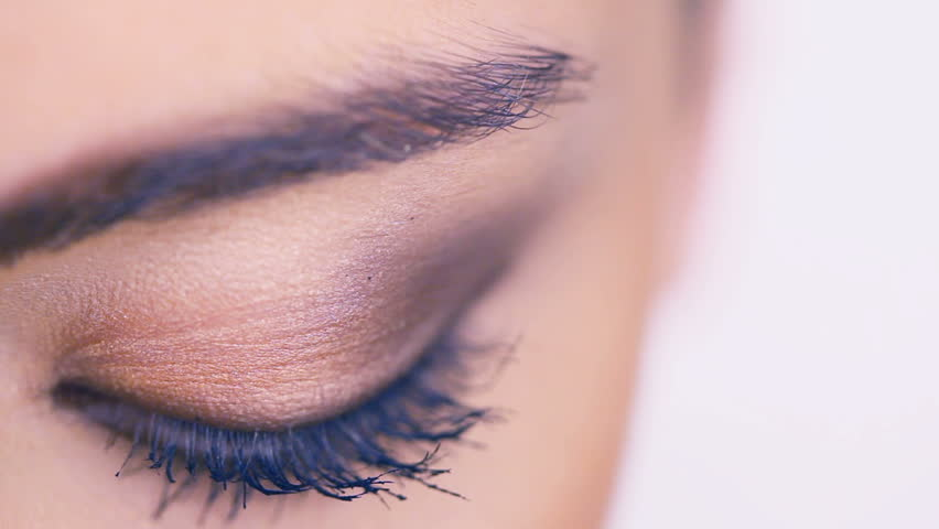 Closeup of a female eye with eyeshadow and long lashes covered in mascara, eyelid closed