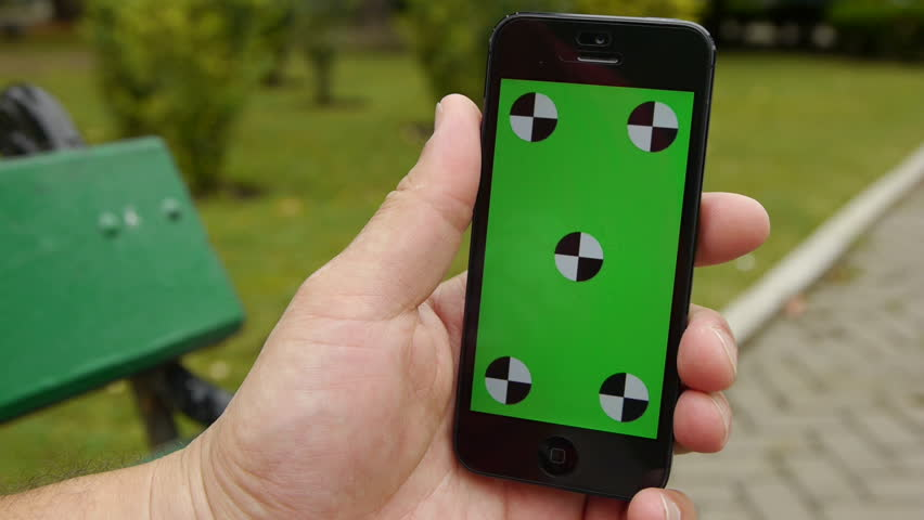 Smart Phone held by hands at the park. Green screen Chroma Key. Close up. Tracking motion. Vertical. Tile floor & green grass background.