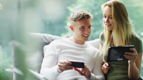 Attractive young couple with technology relaxing together at home