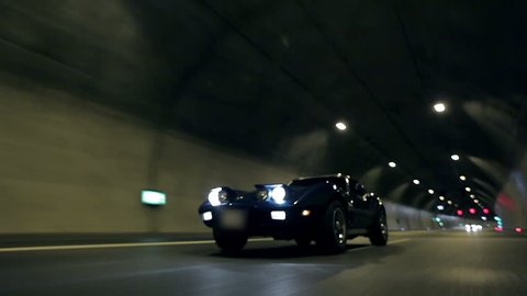 Beautiful low angle shot of Corvette C3 driving through tunnel at night