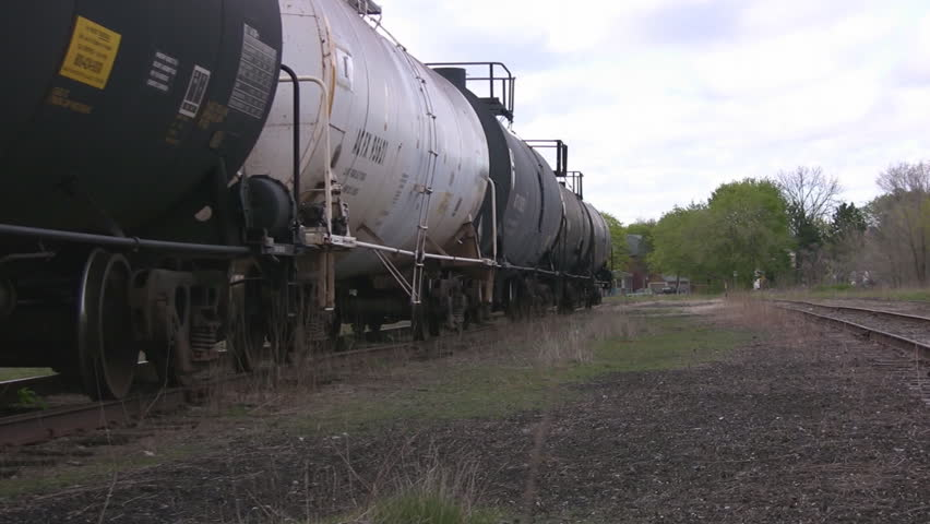 A zoom out along the railroad tracks, highlighting a line of industrial tankers at rest.
