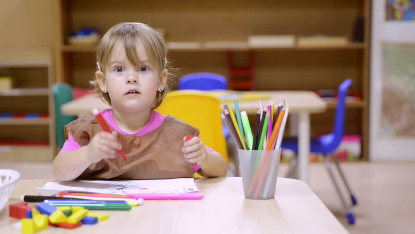 Baby girl laughing and drawing in kindergarten